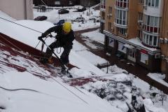 Чистка снега с крыш альпинистами